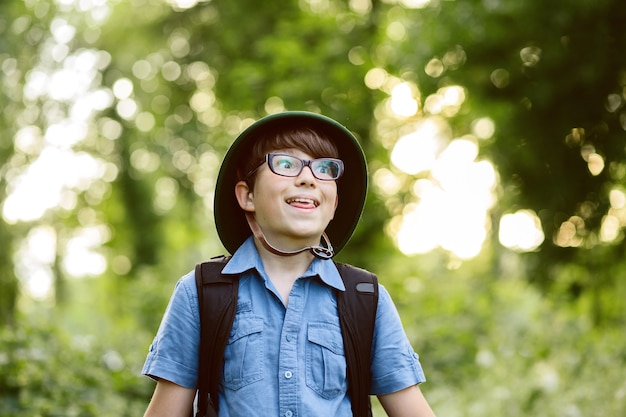 Happy child go hiking with backpack in summer nature