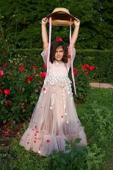 Счастливый ребенок рука вверх, наслаждаясь свободой с летающими лепестками цветов в воздухе. концепция свободы.