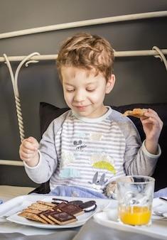 Счастливый ребенок, завтракающий в постели дома утром