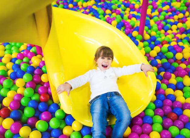 Счастливый ребенок, весело проводящий время в игровой комнате. девушка в детской одежде позирует, сидя на коленях на детской горке