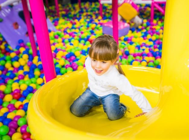 Счастливый ребенок с удовольствием в игровой комнате