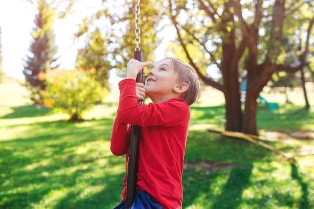 Счастливый ребенок весело на качелях. милый маленький мальчик, играя на прогулке на природе. малыш качается на качелях на детской площадке во дворе.