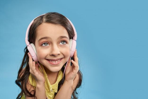 Bambino felice in cuffie che ascolta la musica preferita in studio