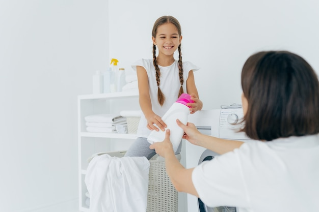 Happy child helper and mother have fun in laundry room, do washing together, smiling girl with two pigtails gives detergent to mum, stands in basket near washing machine. domestic work concept