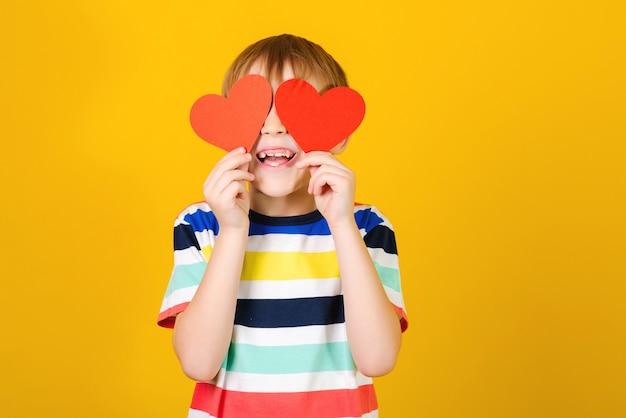 赤い紙の心の後ろに目を隠している幸せな子。休日の概念。赤い紙の心を持ってかわいい笑顔の少年。