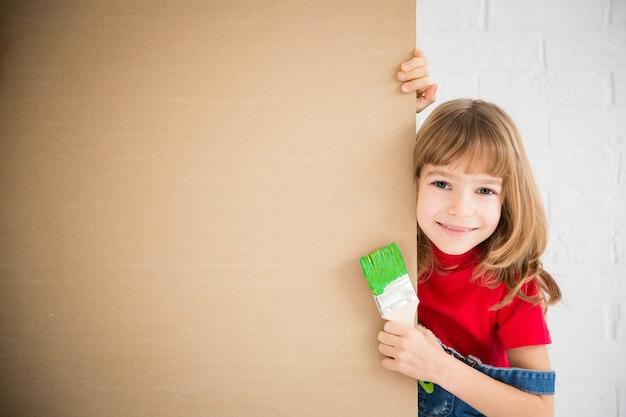 Счастливый ребенок держит пустой знамя. малыш играет дома. весенний ремонт и концепция дизайна