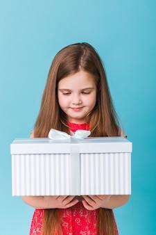 파란색 벽에 생일 선물을 들고 행복 한 아이