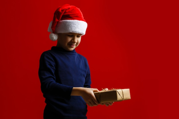 Happy child holding christmas presents on a red background