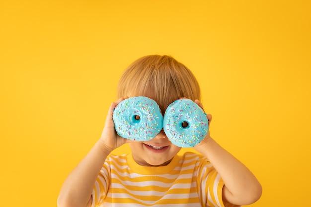 노란색 벽에 유약 된 도넛을 들고 행복 한 아이