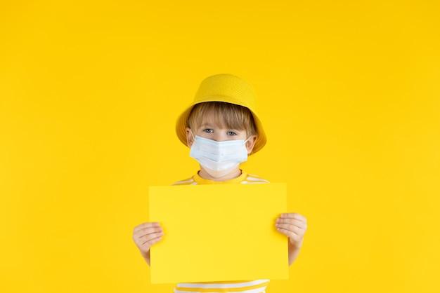 紙の空白を保持している幸せな子。屋内で保護マスクを着用している子供の肖像画。コロナウイルスcovid-19パンデミックコンセプトの夏休み。