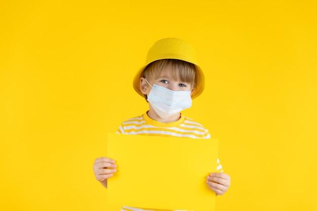 紙の空白を保持している幸せな子。屋内で保護マスクを着用している子供の肖像画
