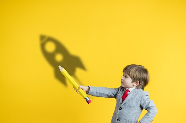 Happy child holding pencil against yellow surface