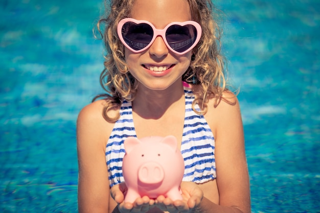 Happy child holding piggybank against blue water wall.