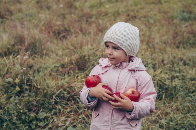 Happy child holding red apples in his hands. harvest funny kid outdoors in autumn park.
