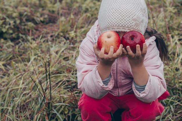 彼の手に赤いリンゴを保持している幸せな子供。秋の公園で屋外面白い子供を収穫します。