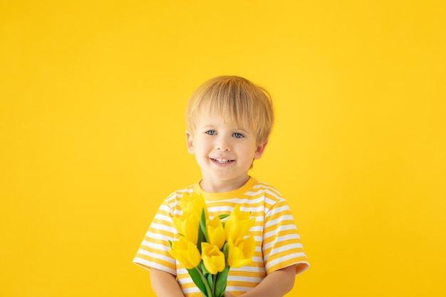 노란색 벽에 튤립의 봄 꽃다발을 들고 행복 한 아이.