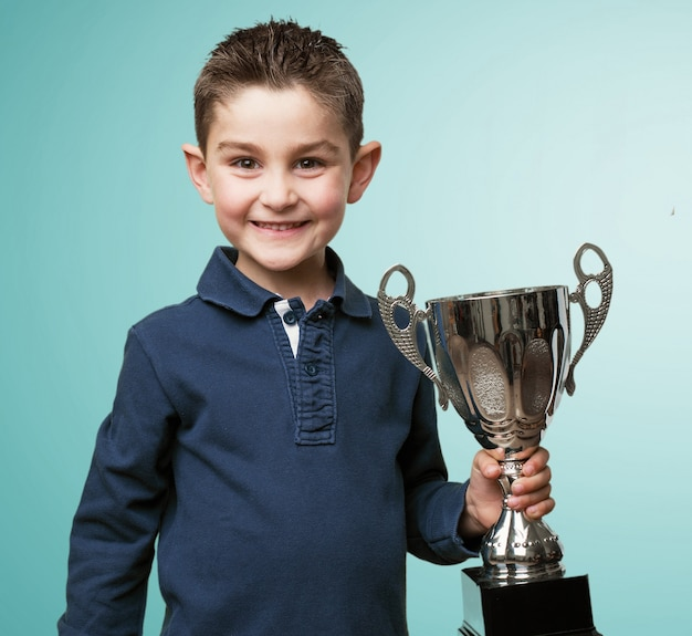 Happy child holding a trophy