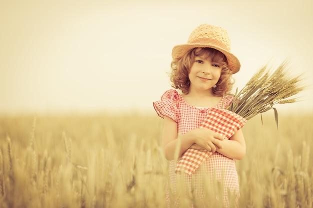 여름 필드에서 밀을 들고 행복 한 아이