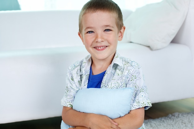 Happy child hugging a pillow