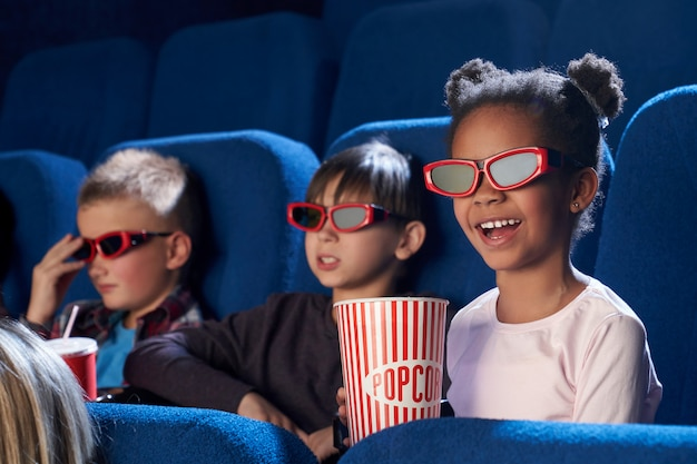 Счастливый ребенок в 3d очках смотрит смешной фильм в кино