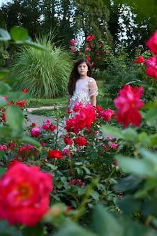 Счастливый ребенок в длинном платье в розовом саду с лепестками цветов в воздухе.