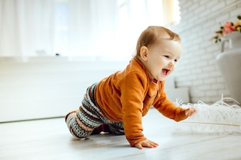 Happy child in orange sweater plays with feather on the floor