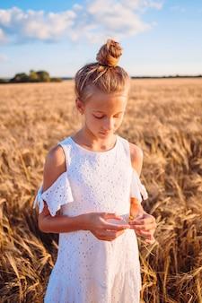 麦畑で幸せな子供。手で熟した小麦と麦わら帽子の白いドレスで美しい少女