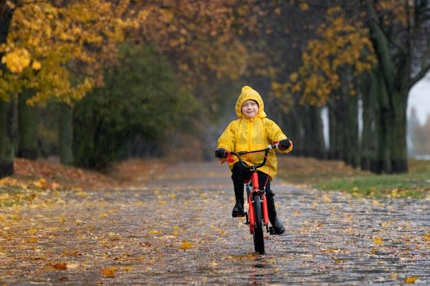 Счастливый ребенок в желтом плаще едет на велосипеде в осеннем парке. мальчик едет по аллее в дождливом парке.