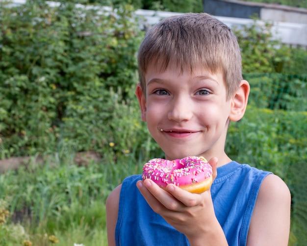幸せな子供は公園でピンクのドーナツを食べています。不健康な食品の概念、甘い食べ物を間食。子供たちは甘い食べ物が大好きです。