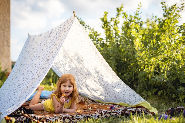 Happy child is lying in a house made of fabric in garden, and eating crackers.