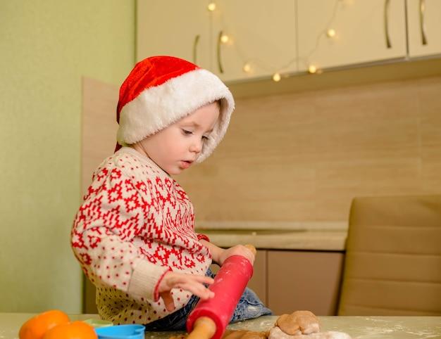 Счастливый ребенок готовит тесто для печенья на кухне