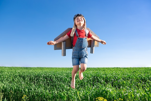 Happy child jumping against blue sky. kid having fun in spring green field outdoor. portrait of boy with paper wings. freedom and imagination concept
