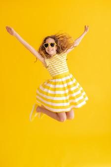 Счастливый ребенок прыгает на желтой летней поверхности