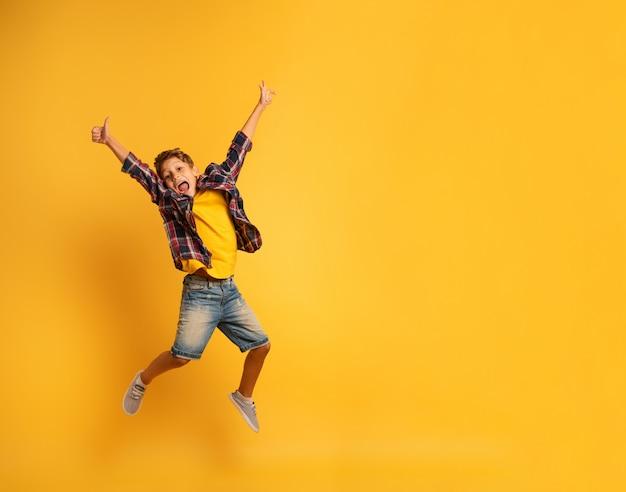 Счастливый ребенок прыгает на желтом фоне