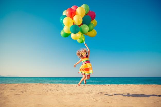 모래 해변에 다채로운 풍선과 함께 점프하는 행복 한 아이 푸른 바다와 하늘에 대 한 재미 있은 여자의 초상화 여름 휴가 자유와 상상력 개념에 재미 활성 아이