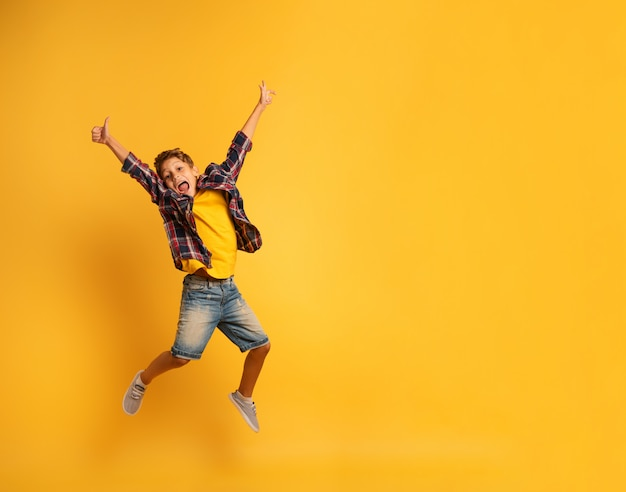 Happy child jumping over a yellow background