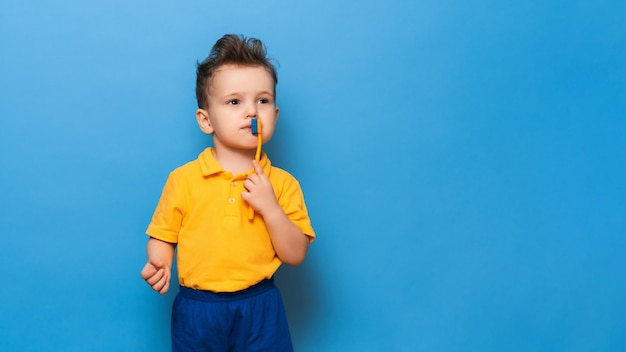 Happy child kid boy brushing teeth with toothbrush on blue background. health care, dental hygiene. mockup, copy space