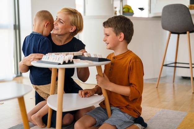 先生と一緒に幼稚園で楽しんで遊んでいる幸せな子供キッズグループ