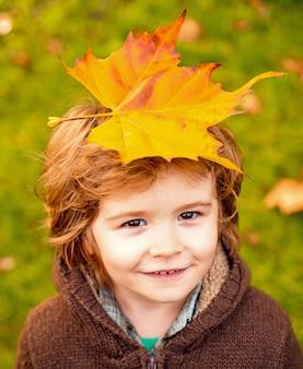 幸せな子笑って、秋の屋外で葉っぱ