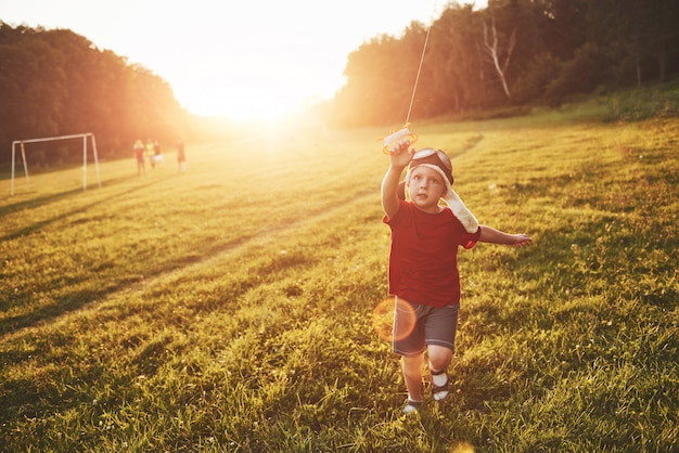 Happy child launch a kite in the field at sunset. little boy and girl on summer vacation