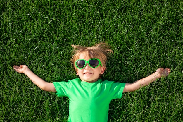 Happy child laying on green grass