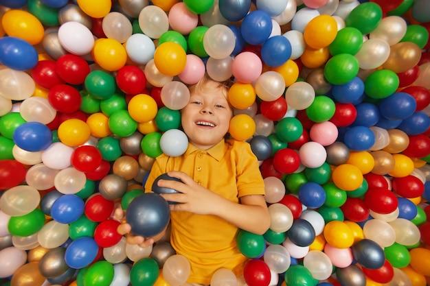 Счастливый ребенок лежит в бассейне и играет с цветными шарами в парке