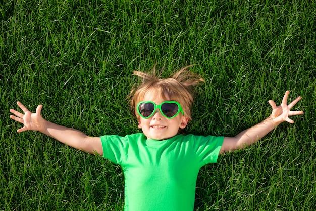 Счастливый ребенок, лежа на зеленой траве. забавный ребенок открытый весной сад. день земли и концепция здорового образа жизни