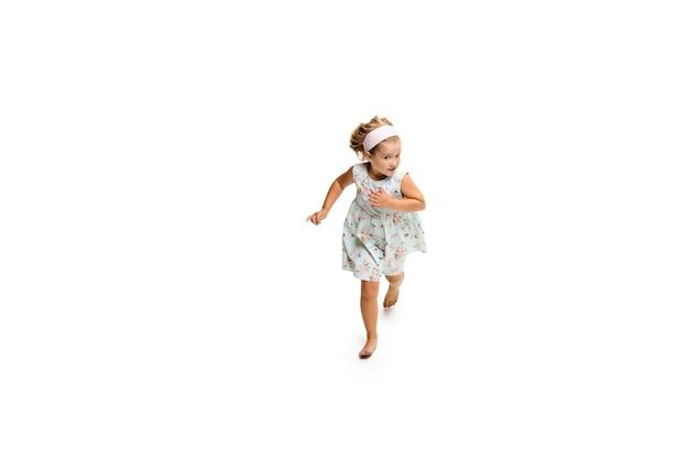 행복한 아이, 작고 감정적인 백인 소녀가 흰색 배경에 격리되어 점프하고 달리고 있습니다. 행복하고 명랑하고 성실해 보입니다. 광고에 대 한 copyspace입니다. 어린 시절, 교육, 행복 개념입니다.