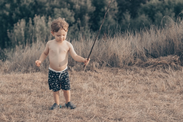 Happy child, little boy playing, pensive look and holding in hands the stick outdoors.