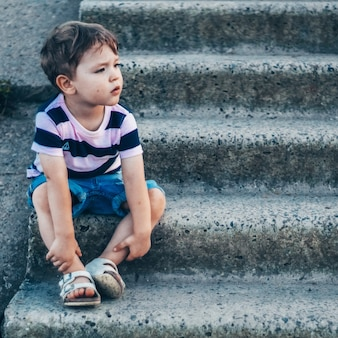 Happy child, little boy sitting on stone steps looks down, pensive look and holding his arms outdoors.