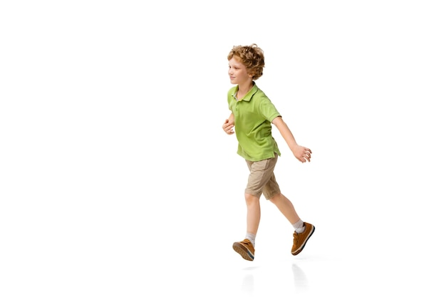 Happy child, little and emotional caucasian boy jumping and running isolated