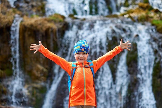 幸せな子供の小さな女の子は、滝の近くでバックパックを持って旅行します。横に手を。アウトドアスポーツの肖像画のクローズアップ