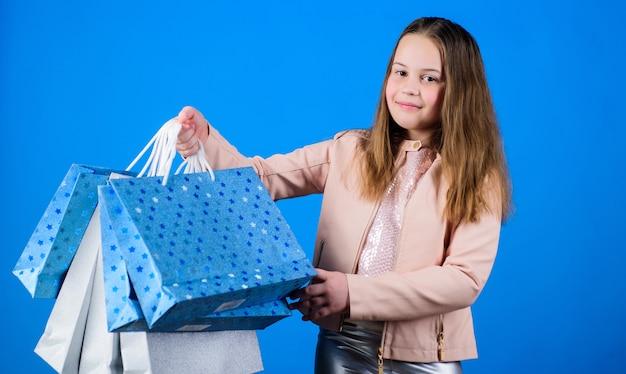 幸せな子。贈り物を持った少女。ショッピングバッグを持つ小さな女の子。販売割引。休日の購入の節約。子供のファッション。パック付き店員。誕生日の買い物。誕生日おめでとう。誕生日プレゼント。