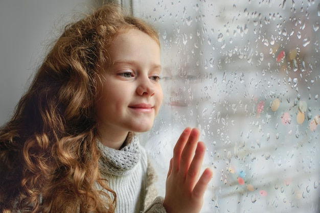 Happy child looking out the window with wet glass autumn bad weather.